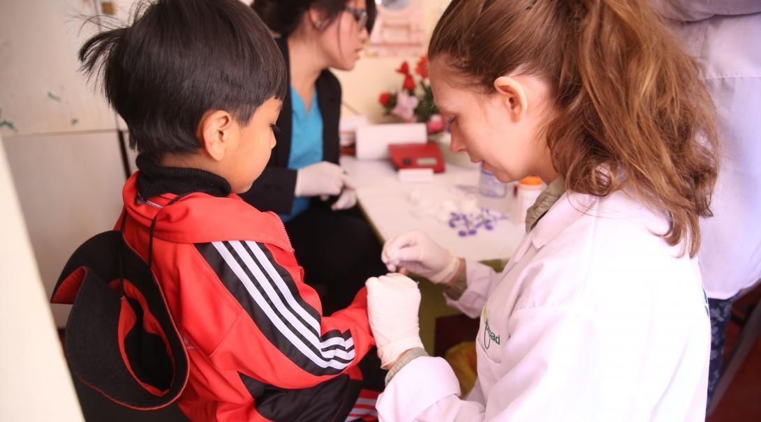Enfermera pasante haciéndole chequeos de salud a un niño pequeño en Perú.